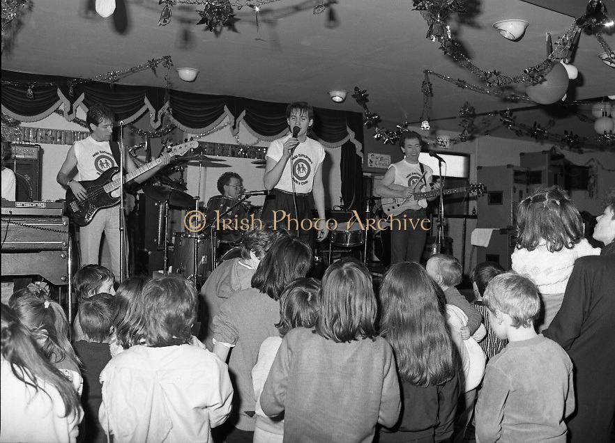 Christmas Party With Johnny Logan..1986..16.12.1986..12.16.1986..16th December 1986..At the 'Embankment',Tallaght, a charity Christmas Party was held for deprived children of the area. The main attraction was the singer and entertainer Johnny Logan,who with his band,entertained the children. Santa Claus took time off from his busy schedule to give a present to all the boys and girls. A great time was had by all...Children of all ages are pictured at the front of the stage as Johnny chats with them.
