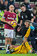 Gaetan Bong (Brighton) receiving treatment on the pitch looked on by Pablo Zabaleta (Capt) (West Ham) & Christopher Kavanagh (Referee) during the Premier League match between West Ham United and Brighton and Hove Albion at the London Stadium, London, England on 2 January 2019.