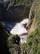 Waves crash at a hole at Pancake Rocks near Pukaiki, West Coast, New Zealand.