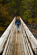 A woman hiker crosses a footbridge in Rogue River National Forest, Oregon