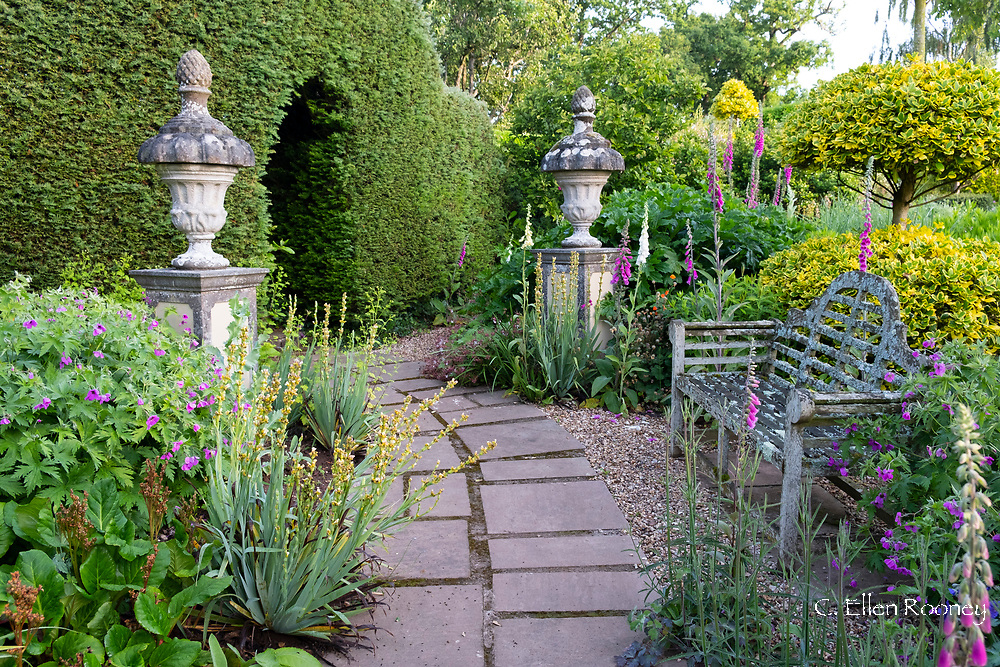 A stone path leading past a Lutyen bench through two stone pillars surrouned by digitalis at the Laskett Gardens, Much Birch, Herefordshire, UK