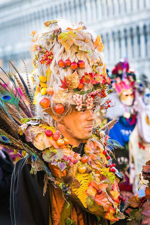 man wearing costume decorated in fruits and berries is seen walking through St Mark's square during Venice carnival.