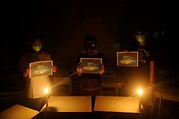 Medan, Indonesia, March 28, 2020: Indonesian people seen using masks and hold posters under the candle lighting in the small campaign action to welcoming Earth Hour moment to resting the earth from the electrical energy used and avoid the harmfull effects of climate changes that trigger the emergence of Corona Virus Disease 19, Photo taken in journalism campus of STIKP in Medan, North Sumatra province, Indonesia on March 28, 2020.