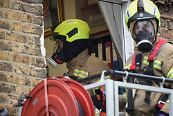 © Licensed to London News Pictures. 01/04/2020. London, UK. Firefighters wearing full respirators normally used to protect against smoke inhalation on an aerial platform at an incident involving all emergency services where a suspected COVID-19 case <br /> removed from their home. Uxbridge Road in Shepherd's Bush was closed for an hour as ambulance, fire brigade and police attended, extracting the patient by crane from a three story apartment building in West London. PPE (personal protective equipment) was in evidence, with the fire brigade using full facerespirators normally reserved for firefighting. A police officercommented the Metropolitan police force are issued only with rubber gloves. Ambulance workers decontaminated the scene and reusable equipment before moving on.  Photo credit: Guilhem Baker/LNP