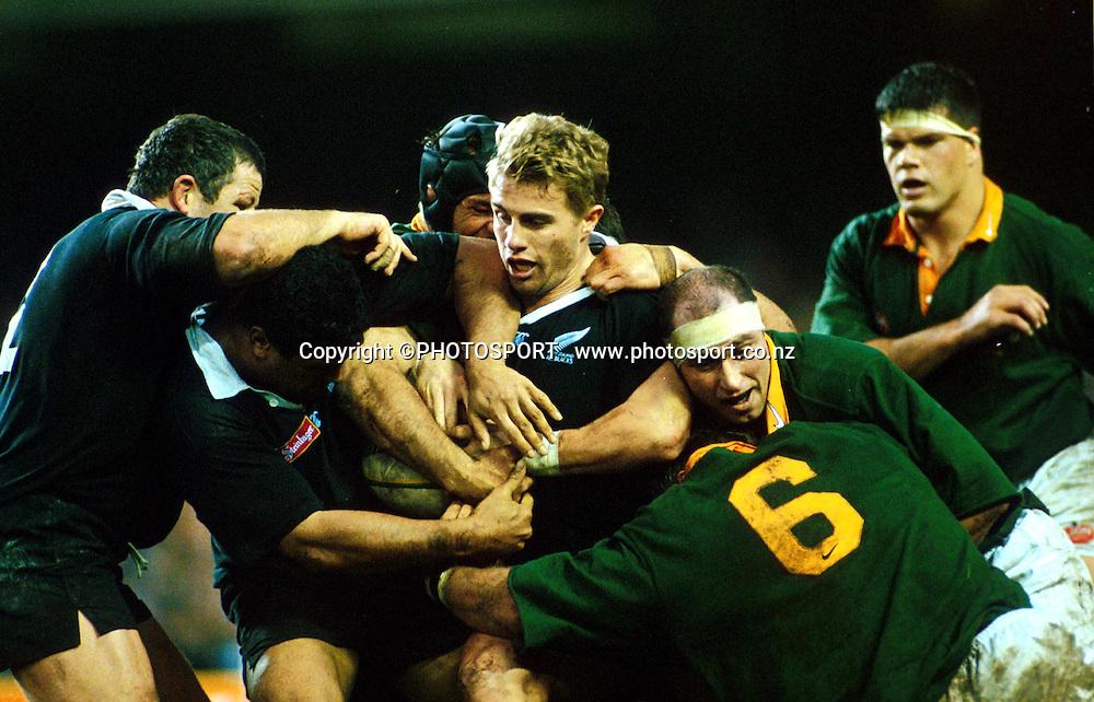 Justin Marshall holds desperately to the ball, New Zealand All Blacks v South Africa, 1996. Photo: Andrew Cornaga/PHOTOSPORT