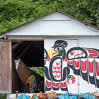 Building decorated with traditional First Nation mural artwork holding a wooden canoe in the tiny village of Alert Bay, Cormorant Island, British Columbia, Canada.