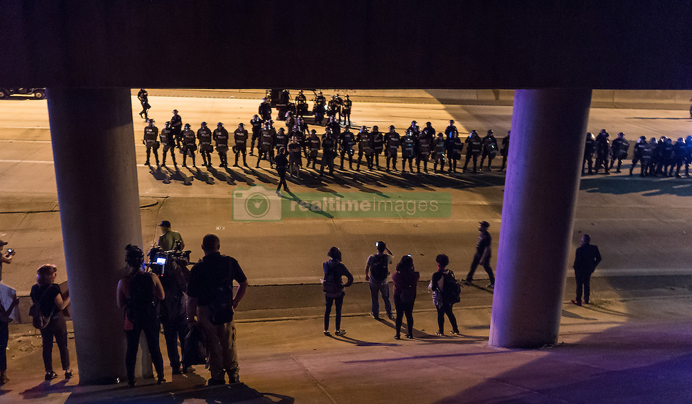 September 22, 2016 - Charlotte, North Carolina, United States of America - September 22, 2016 - Charlotte, NC, USA - Riot police and protestors gather on the highway during a third day of protests in Charlotte, North Carolina on Thursday, Sept. 22, 2016. This is the third day of protests that erupted after a police officer's fatal shooting of an African-American man Tuesday afternoon and the first full day of a declared State of Emergency by the governor. (Credit Image: © Sean Meyers via ZUMA Wire)