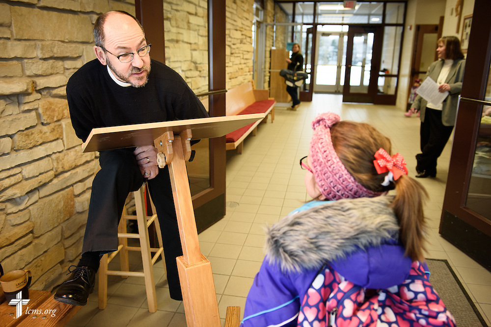 The Rev. Peter Bender quizzes Elizabeth Vogt on the Sacrament of Holy Baptism before morning chapel at Peace Lutheran Academy, part of Peace Lutheran Church in Sussex, Wis., on Monday, Feb. 8, 2016. LCMS Communications/Erik M. Lunsford