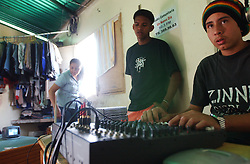 "Davis Semeco, right, plays music during his radio show on ""A New Day Radio"", a community radio station in Caracas.  The station operates out of a home in a Caracas slum. Chavez and his government have been increasingly supportive of these generally Chavista community media stations as a response to the anti-chavista private media."