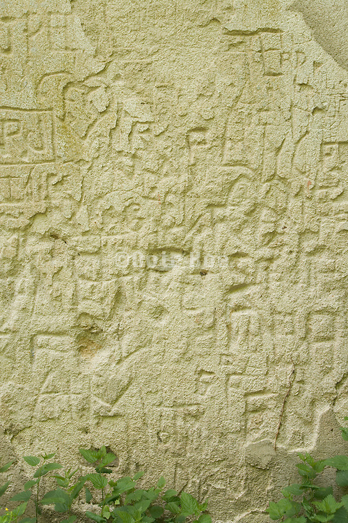 a wall with old carved graffiti markings
