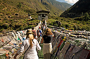BU00006-00...BHUTAN - Tour group and guide crossing a famous chain link bridge, first made by the Iron Bridge Lama, (Thangtong Gyalpo (1385-1464)), over the Paro River. The bridge has been remade using some of the original chain links. Cave on the hill may have been the source of the iron used in the chain links.