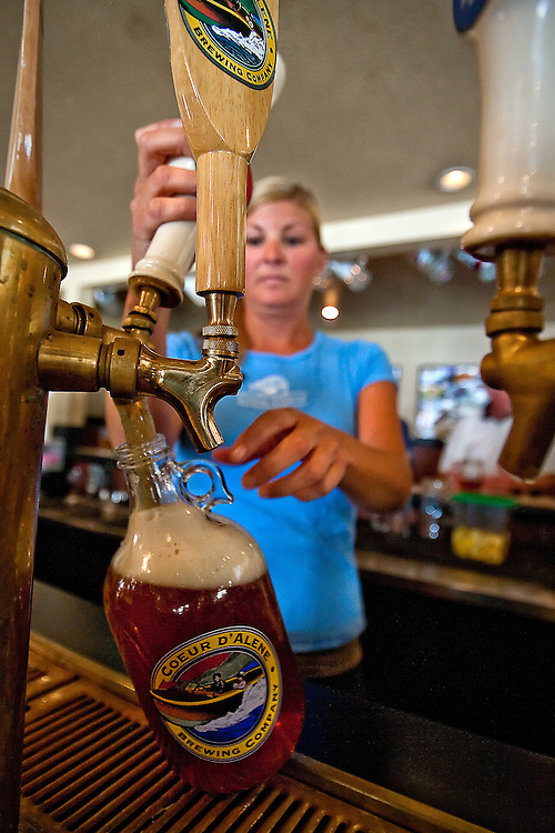Coeur d'Alene Brewing Company bartender Kari Sorum fills up a growler of Centennial Pale Ale for a customer Wednesday evening. The Cd'A Brewing Company will close its 209 Lakeside Avenue doors after 23 years of serving the Coeur d'Alene community finely-crafted, locally-brewed beers.