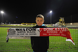 A fan poses for a photo inside the Woodspring Stadium with his scarf which reads Weston super mare vs Doncaster Rovers. - Photo mandatory by-line: Alex James/JMP - Mobile: 07966 386802 - 18/11/2014 - SPORT - Football - Weston-super-Mare - Woodspring Stadium - Weston-super-Mare v Doncaster - FA Cup - Round One