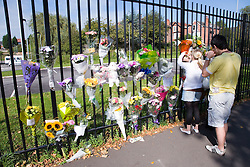 People placing memorial flowers on railings,