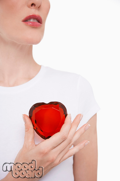 Woman holding heart-shaped jewel between finger and thumb
