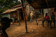 MONTE PLATA PROVINCE, DOMINICAN REPUBLIC - OCTOBER 11, 2013: Men wait for a truck to take them to cut sugar cane at a bus stop in an impoverished batey on a sugar cane plantation in Monte Plata.