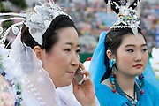 The annual Lotus Lantern Festival is held to celebrate Buddha's Birthday. Opening ceremony for the parade at Dongdaemun Stadium. Lady with mobile phone.