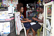 Esther Igwe training another lady in how to make beaded decorations in her shop 'Goshen Decorates', where she makes and sells decorations for parties and events, Nigeria.<br /> <br /> Esther attended a business training workshop with Youth for Technology and also signed up to receive the business support texts.<br /> <br /> She has learnt a lot from the course and the text messages; including business planning, capital investment, diversifying incomes streams and improving customer relationship management. She says profit is up 40% as a result, that her confidence has improved.<br /> <br /> Esther started her business in 2010 because she had given birth to twins and with her previous three children the family were struggling financially.