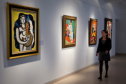 © Licensed to London News Pictures. 04/04/2013. London, UK. A Christie's employee walks past paintings including Andre Derain's 1905 portrait of the wife of Henri Matisse entitled 'Madame Matisse au kimono' (est. US$15,000,000-20,000,000) (second from left); Fernand Leger's 'Les deux figures' (1929, est. US$3,000,000-5,000,000) (L); and Pablo Picasso's 'Buste d'homme a la pipe' (1969, est US$900,000-1,200,000) (2nd from right) at an auction press preview in St James, London, today (04/04/2013). The sale, consisting of Impressionist & Modern Art, is set to take place  on the 8th of May in Christie's New York premises.  Photo credit: Matt Cetti-Roberts/LNP