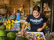 10 OCTOBER 2016 - UBUD, BALI, INDONESIA:  A woman makes floral decorations in her shop in the Ubud market. The morning market in Ubud is for produce and meat and serves local people from about 4:30 AM until about 7:30 AM. As the morning progresses the local vendors pack up and leave and vendors selling tourist curios move in. By about 8:30 AM the market is mostly a tourist market selling curios to tourists. Ubud is Bali's art and cultural center.     PHOTO BY JACK KURTZ