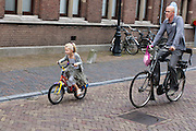 Een man fietst met zijn dochtertje door het centrum van Utrecht na afloop van de eerste ochtend op school.<br /> <br /> A man is cycling with his daughter in Utrecht