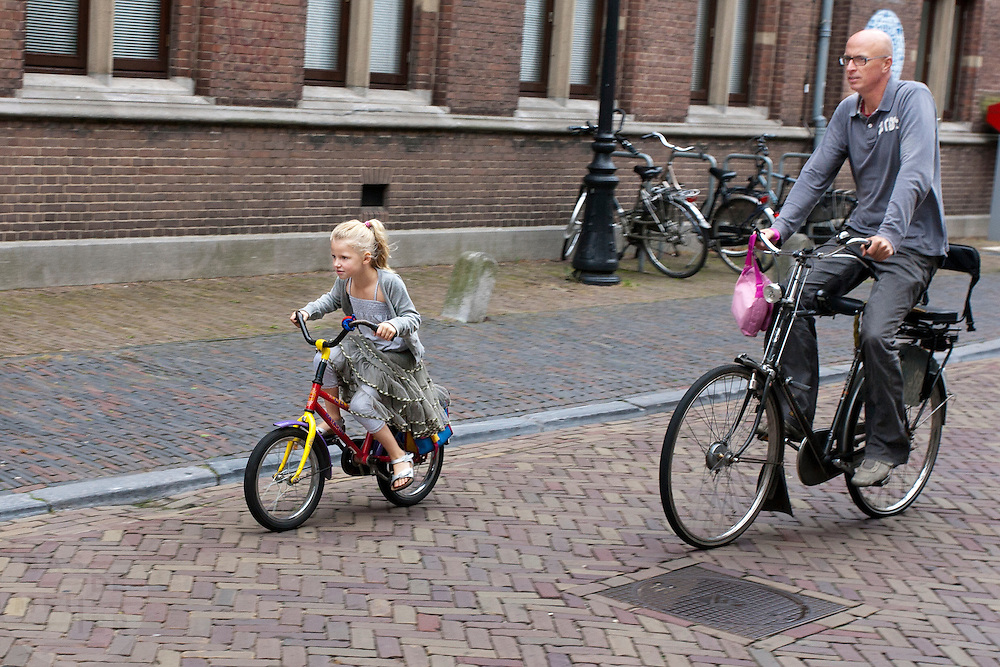 Een man fietst met zijn dochtertje door het centrum van Utrecht na afloop van de eerste ochtend op school.<br /> <br /> A man is cycling with his daughter in Utrecht