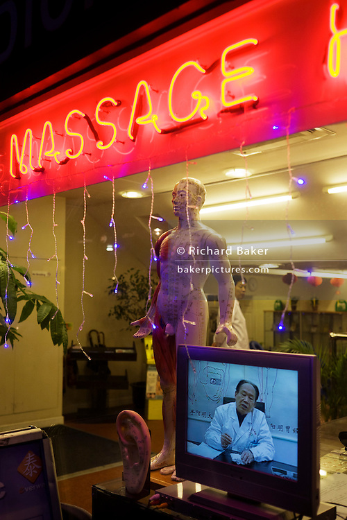 Doctor on TV screen at a traditional Chinese herbalist's shop window in London's West End.