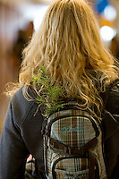 A woman carries a fir seedling in her backpack from a display booth, while attending the Science World traveling science exposition in Campell River,Vancouver Island, British Columbia, Canada.