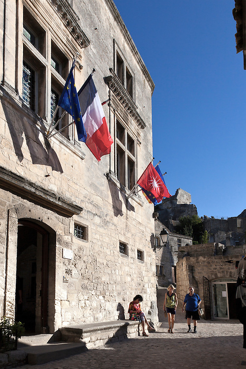 Unidentified tourists navigate one of the narrow streets in Les-Baux-de-Provence.  This ancient village has dominated its small mountain top since the 10th century.  Its narrow streets and tiny buildings now house shops, eateries, and museums, and host upwards of two million visitors annually.