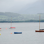 Five sailboats anchored and moored off Beaumaris on the island of Anglesey of the north coast of Wales, UK.