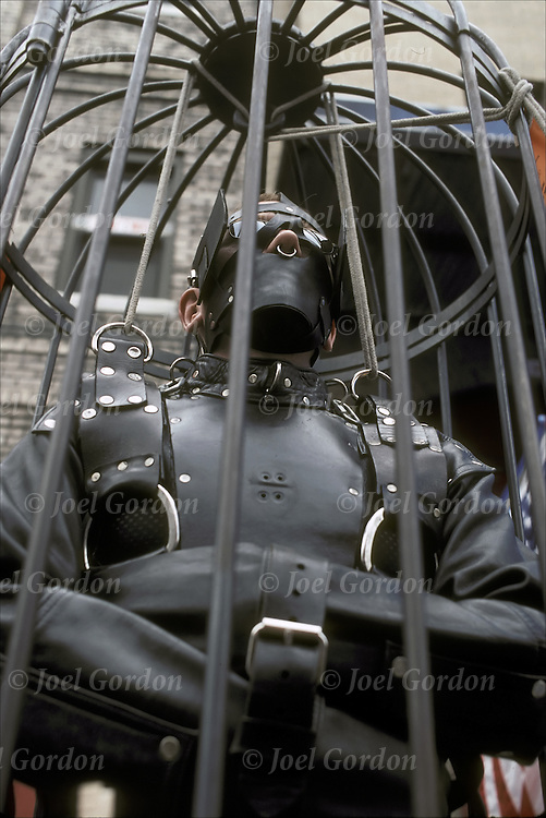 Slave handcuffed, locked in Cage,dressed in S&M paraphernalia, bondage, the annual  S & M Folsom Street Fair