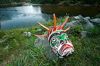 A Native mask depicting one of the underwater spirits in  First Nations legend rests beside the banks of the Puntledge river in Courtenay,  Courtenay, The Comox Valley, Vancouver Island, British Columbia, Canada.