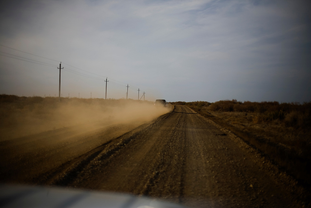 CREDIT: DOMINIC BRACCO II..SLUG:PRJ/KAZAKHSTAN..DATE:10/30/09..CAPTION:A jeep kicks up dust on the road to the Dike Kokaral on October 30, 2009 near Aralsk, Kazakhstan. The Dike Kokaral was completed in 2005 to help combat the Aral Sea's diminishing waters...Aral Sea Overview: ..During the 1960s the USSR began irrigating the waters of the Aral Sea in southern Kazakhstan to combat their growing food crisis. The Soviets severely miscalculated and water began receding quickly from the port cities. The waters continued to recede. By 2000 the water was 80 km away from the city of Aralsk, a main seaport in Kazakhstan. In 2005 with help from the World Bank, construction began on a 13km dike that locals hoped would bring the waters back to their original shores. The project raised water quality and fishing was able to resume, however four years after completion of the dike the water is still 50km from Aralsk's port. Locals seem mixed on the possibility of the sea returning after more than 40 years without the sea. Fishermen from Aralsk make a three-hour path through soft desert road along the former seabed. The only source of income for many is cattle, horses, and camels, which have, began to overgraze the areas of the former seabed and surrounding desert. Because of this nutrient rich topsoil is lifted by the wind and the process of desertification continues.  .