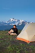 Hiker enjoying the evening at backcountry campsite on Skyline Divide, Mount Baker Wilderness Washington