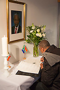 Brussels Belgium 6th December 2013. At the South African Embassy in Brussels people gather. Nelson Mandela died just yesterday. man looking as mandela signs the book