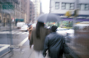 Two people walking a city street in the rain