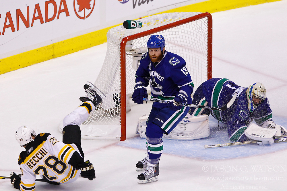 June 15, 2011; Vancouver, BC, CANADA; Boston Bruins left wing Mark Recchi (28) is knocked to the ice by Vancouver Canucks left wing Raffi Torres (13) during the second period of game seven of the 2011 Stanley Cup Finals at Rogers Arena. Boston defeated Vancouver 4-0. Mandatory Credit: Jason O. Watson / US PRESSWIRE