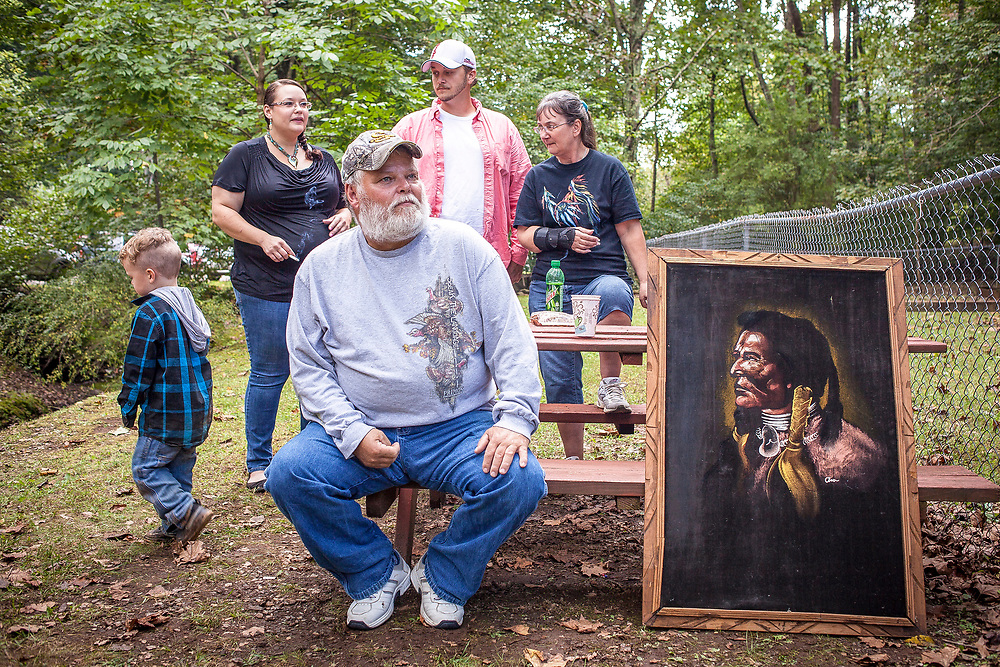 Tim Beverly sits on a picnic bench with a painting he bought for $30 during the Monacan Homecoming at the Tribal Center, in Amherst, VA, on Saturday, October 01, 2016.  Beverly doesn't have a tribal card but both his parents are Monacan.  He attributes his lack of a card on the difficulty of proving ancestry in the 20th century in the aftermath of the 1924 Racial Integrity Act in Virginia, which made it impossible for Native Americans to acknowledge their heritage on any of their official documents. John Boal Photography