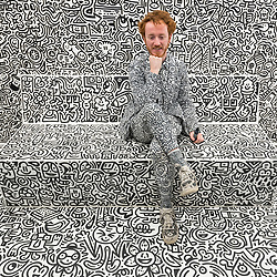 """© Licensed to London News Pictures. 07/04/2018. LONDON, UK. The artist Mr Doodle poses againts his distinctive artwork in The Doodle Room at """"Sense of Space"""", an art pop-up which has opened to the public in Broadgate.  Comprising four rooms to challenge the visitor's sensory perceptions through art, the installation is open until 18 May.  Photo credit: Stephen Chung/LNP"""