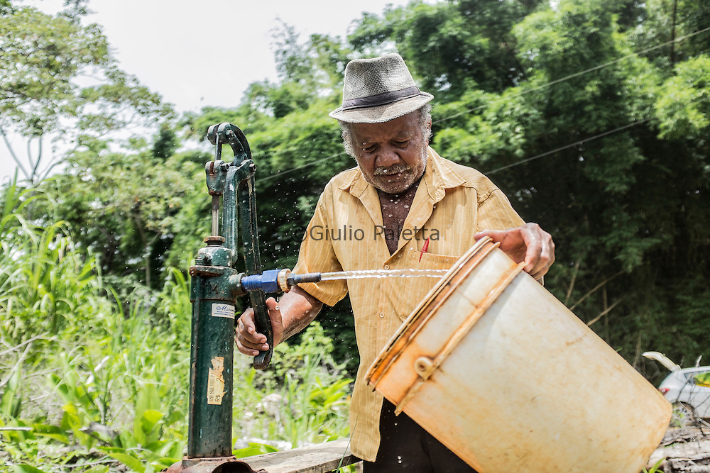 Antonio Honorato , 73, pumps the yellowish contaminated waters, full of iron, that he boils before drinking