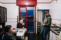 TARANTO, ITALY - 22 FEBRUARY 2018: Alessio Peretto (center, 42), who has worked at the ILVA steel mill since 2002 but is nonetheless part of activist group trying to shut it down, is seen here arguing with his uncle and aunt over who to vote in the upcoming Italian General Election, in their 10th floor apartment in the working-class district of Tamburi that looks directly over the neighborhood and on to the steel mill, in Taranto, Italy, on February 22nd 2018.<br /> <br /> Taranto, a  formerly lovely town on the Ionian Sea has for the last several decades been dominated by the ILVA steel mill, the largest steel plant in Europe. It was built by the government in the 1960s as a means of delivering jobs to the economically depressed south, but has been implicated for a cancer as dioxin and mercury have seeped into local groundwater, tainting the food supply, while poisoning the bay and its once-lucrative mussels.