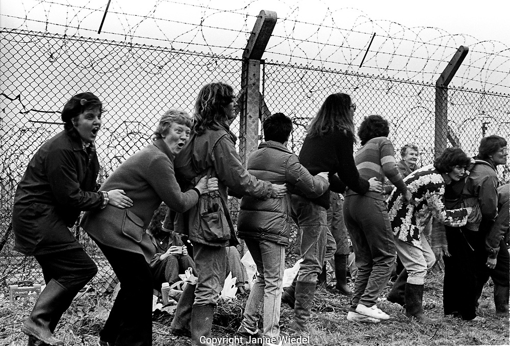 Women surrounding the baseduring protest at  Anti-nuclear Greenham Common Women's Peace Camp in 1983 / 1984. The women only camp surrounded the RAF  base in Berkshire (UK) where American cruise missiles were being stored.