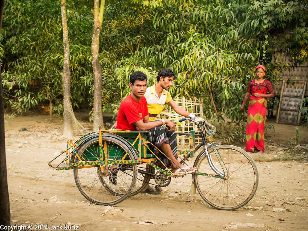 05 NOVEMBER 2014 - SITTWE, RAKHINE, MYANMAR: A rickshaw hauls a passenger through a Rohingya IDP camp near Sittwe. After sectarian violence devastated Rohingya communities and left hundreds of Rohingya dead in 2012, the government of Myanmar forced more than 140,000 Rohingya Muslims who used to live in and around Sittwe, Myanmar, into squalid Internal Displaced Persons camps. The government says the Rohingya are not Burmese citizens, that they are illegal immigrants from Bangladesh. The Bangladesh government says the Rohingya are Burmese and the Rohingya insist that they have lived in Burma for generations. The camps are about 20 minutes from Sittwe but the Rohingya who live in the camps are not allowed to leave without government permission. They are not allowed to work outside the camps, they are not allowed to go to Sittwe to use the hospital, go to school or do business. The camps have no electricity. Water is delivered through community wells. There are small schools funded by NOGs in the camps and a few private clinics but medical care is costly and not reliable.   PHOTO BY JACK KURTZ