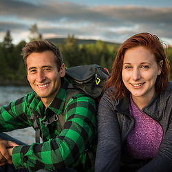 A young couple next to Long Pond in Maine's north woods. Near Greenville, Maine.