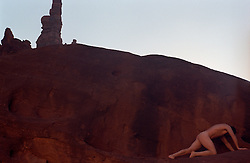 Nude Man  on a red desert cliff In Mohab, Utah