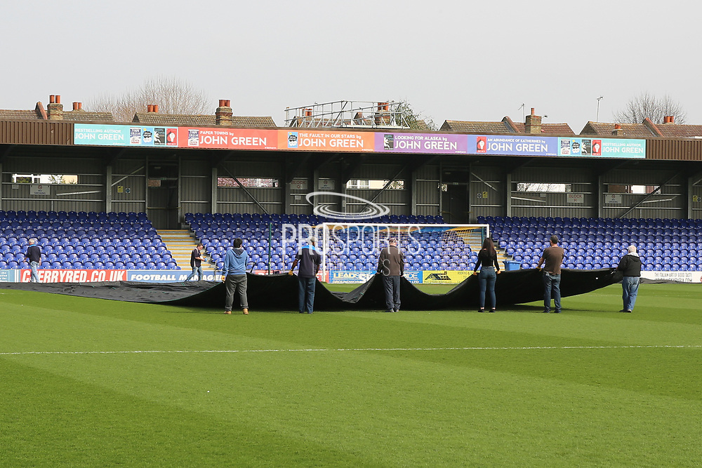 Removing the cover from AFC Wimbledon pitch during the EFL Sky Bet League 1 match between AFC Wimbledon and Northampton Town at the Cherry Red Records Stadium, Kingston, England on 11 March 2017. Photo by Matthew Redman.