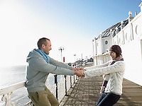 Couple holding hands spinning around on deck of pier