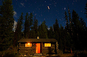 Silvertip Cabin at night with a commercial jet airliner flying overhead during a full moon. From my 2013 Artist-in-Wilderness Connection prgram residency run by the Flathead National Forest, Hockaday Museum of Art, Bob Marshall Wilderness Foundation and the Swan Ecosystem Center. Flathead National Forest, northwest Montana.