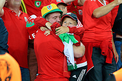 LILLE, FRANCE - Friday, July 1, 2016: A Wales supporter hugs his two children as he celebrates the 3-1 victory against Belgium at full time after the UEFA Euro 2016 Championship Quarter-Final match at the Stade Pierre Mauroy. (Pic by Paul Greenwood/Propaganda)