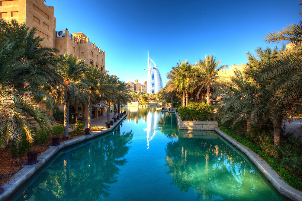 The Burj Al Arab in Dubai rises over the beautifully built canals of a popular area.